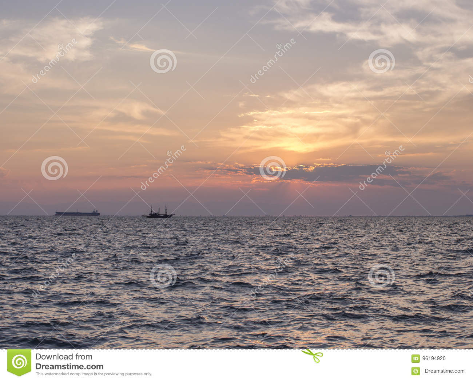 Ein Sonnenuntergang über dem Meer mit zwei Schattenbildern von Schiffen