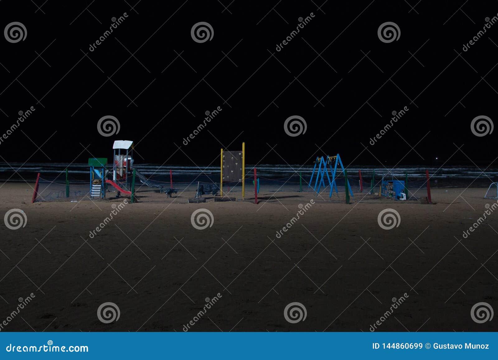 Ein Spielplatz der Kinder im Sand des Strandes von Essaouira nachts belichtet mit Scheinwerfern