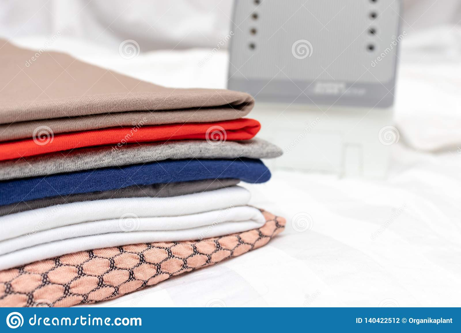 Ein Stapel mehrfarbige Kleidung nah oben mit dem weißen modernen elektrischen Eisen des Hintergrundes - Bügeln, Wäscherei und Hau
