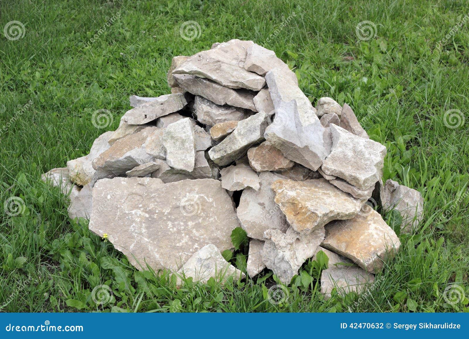 Ein Stapel von rauen Felsen auf dem grünen Gras