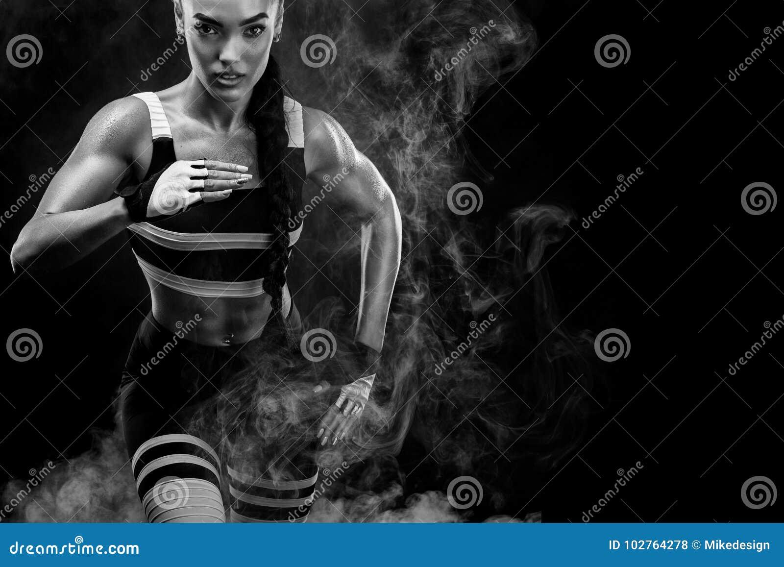 Ein starker athletischer, weiblicher Sprinter, laufend bei dem Sonnenaufgang, der im Sportkleidungs-, Eignungs- und Sportmotivati