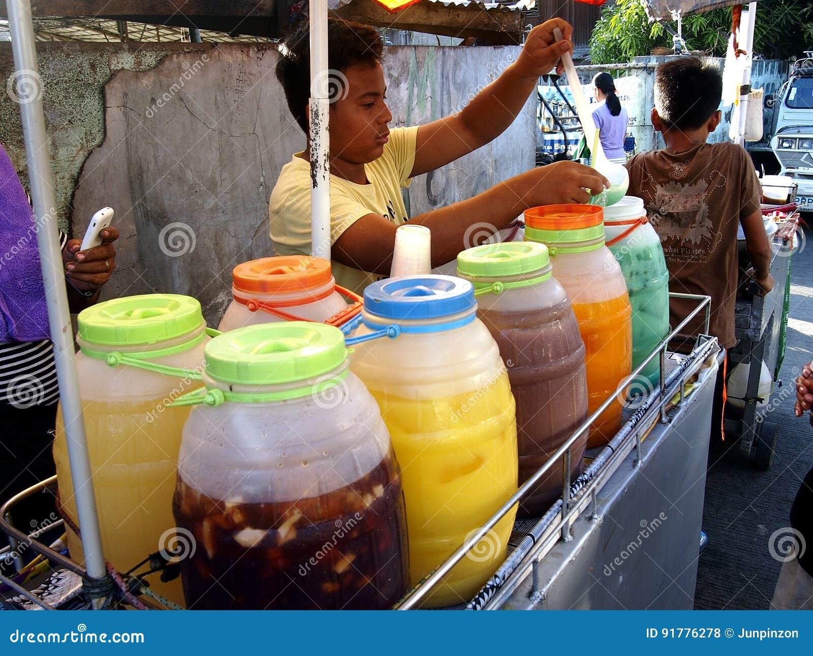 Ein Straßenhändler verkauft eine Vielzahl des Fruchtsaftes und anderer Erfrischungen auf seinem Getränkewarenkorb an einer Straße