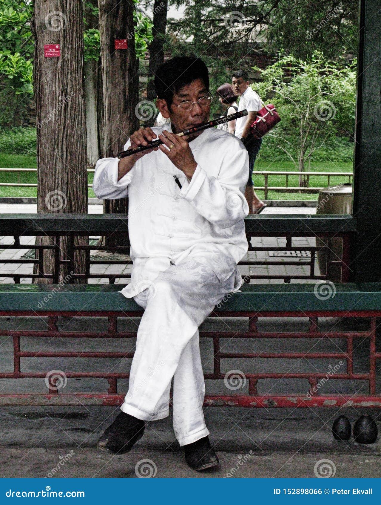 Ein Straßenmusiker spielt traditionelle Flöte