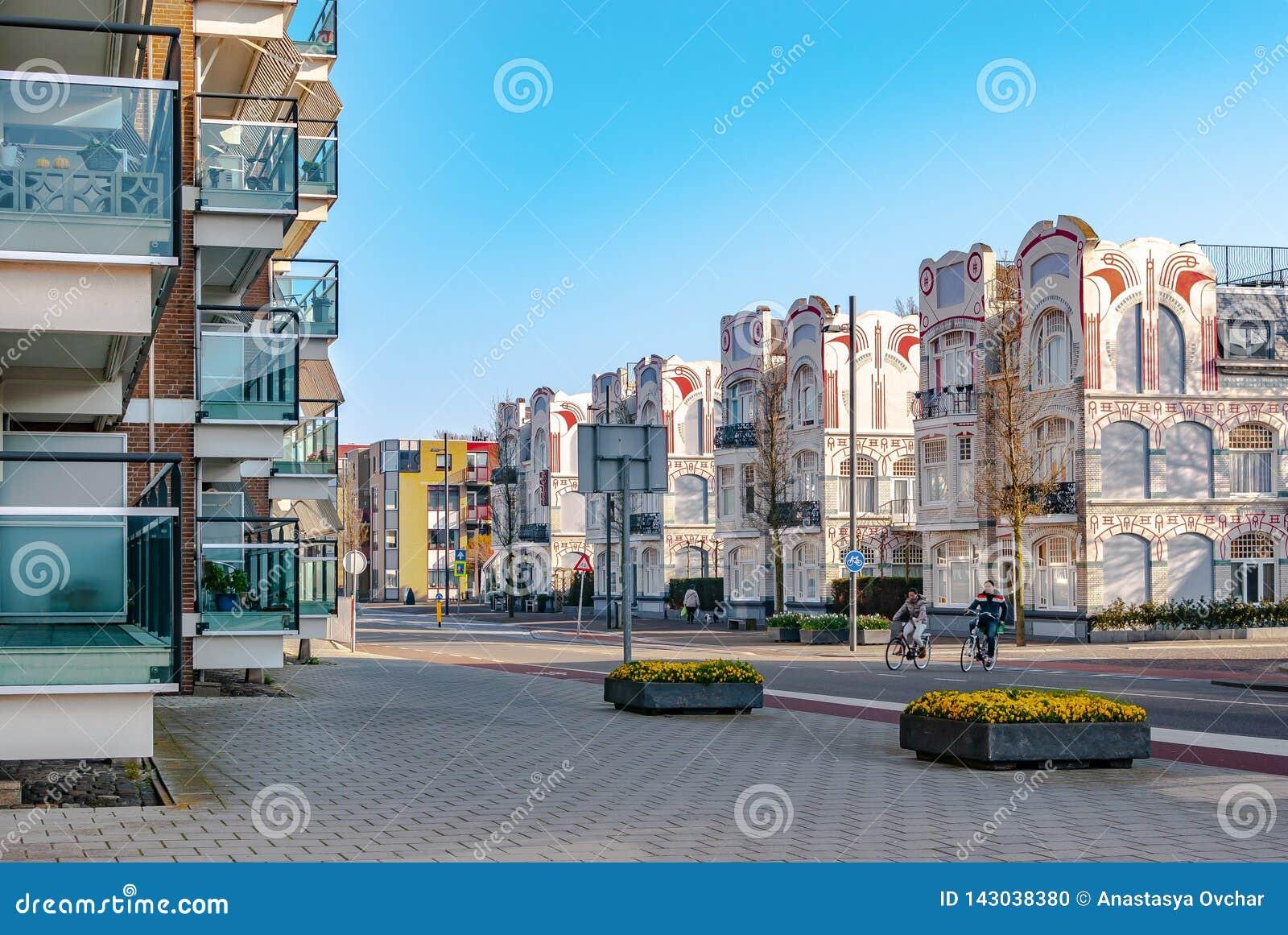 Ein streetview mit modernen Wohnungen auf den linken und historischen Jugendstilhäusern auf rechter Seite Zwei Fahrräder kreuzen