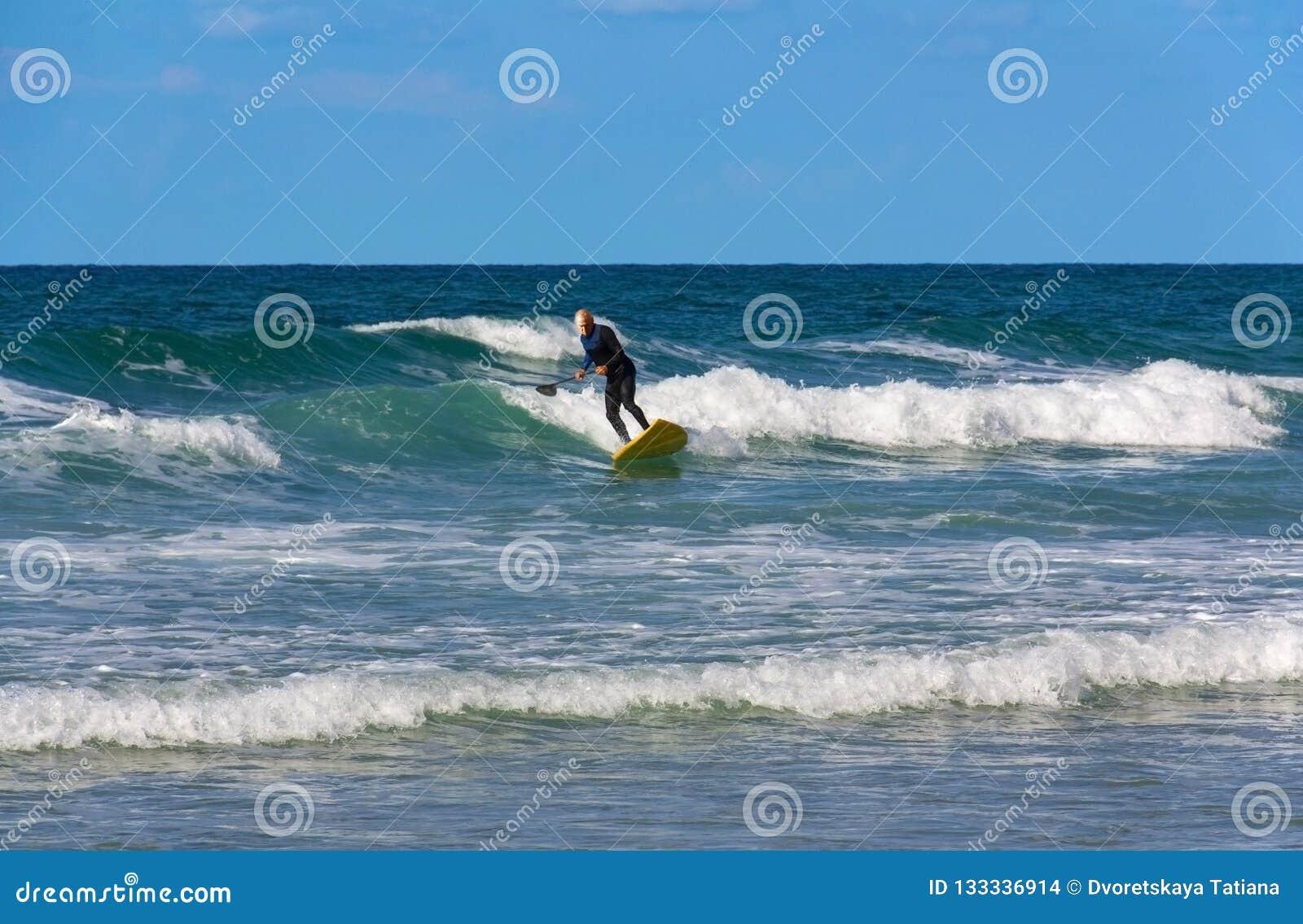 Ein Surfer über dem Alter von 60 Dias auf den Wellen