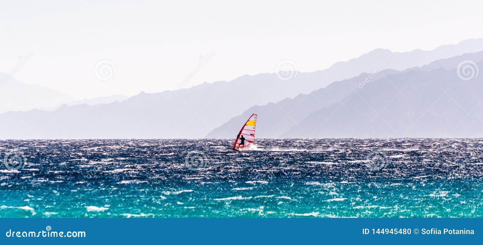 Ein Surfer fährt auf einen Hintergrund des Hochgebirges in Ägypten Dahab Süd-Sinai