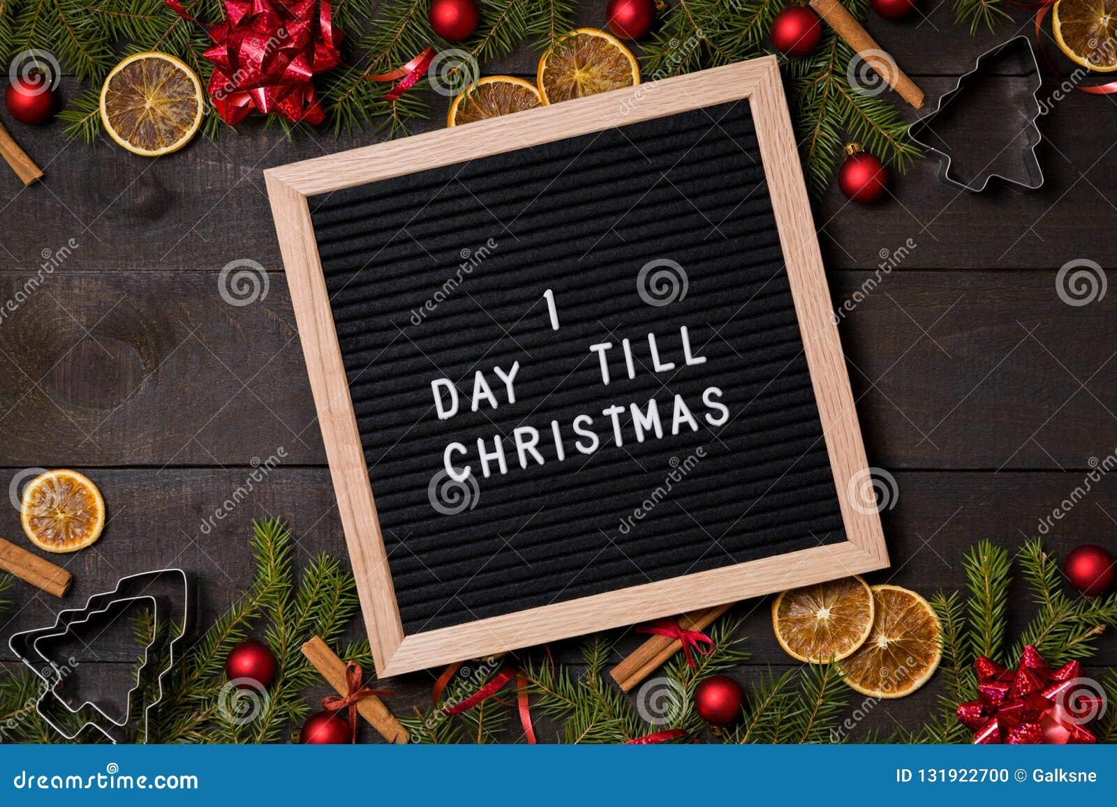 Ein Tag bis Weihnachtscountdown-Buchstabebrett auf dunklem rustikalem Holz