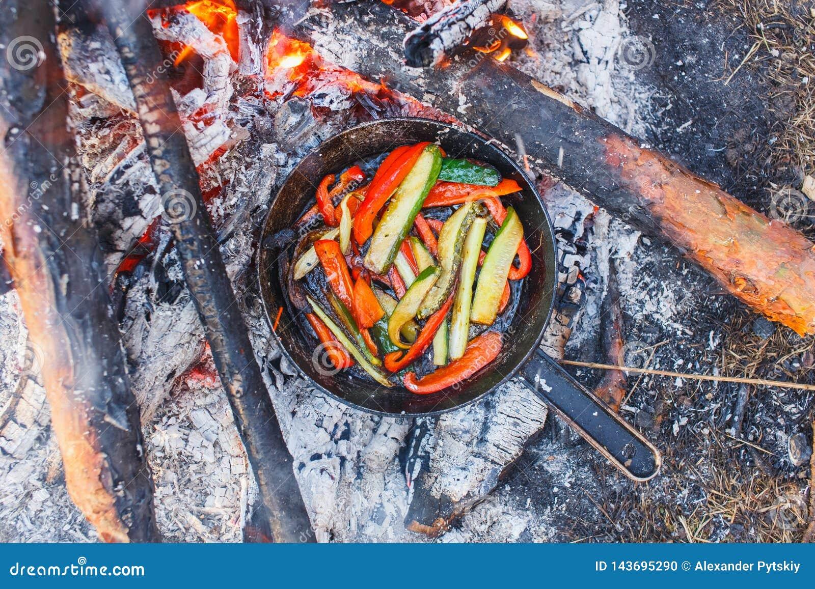 Ein Teller des roten grünen Pfeffers und der Gurken in einer Wanne auf einem Feuer