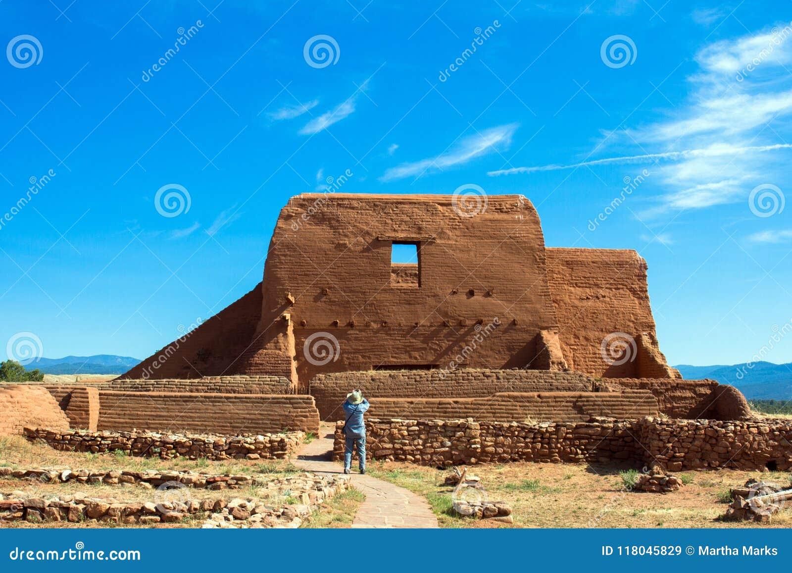 Ein Tourist fotografiert die historische Auftragkirche in nationalem historischem Park PECO im Nordnew mexico