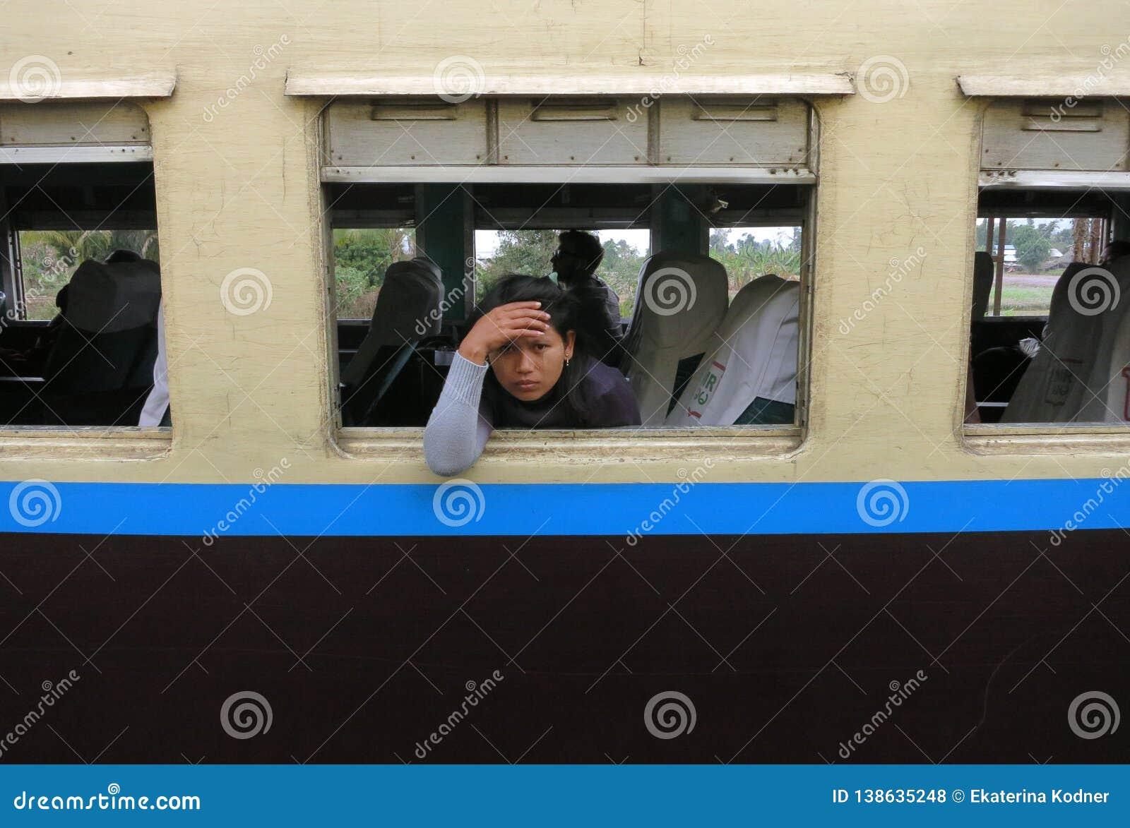 Ein trauriges und müdes birmanisches Mädchen, das aus dem Fenster eines alten Zugs heraus schaut