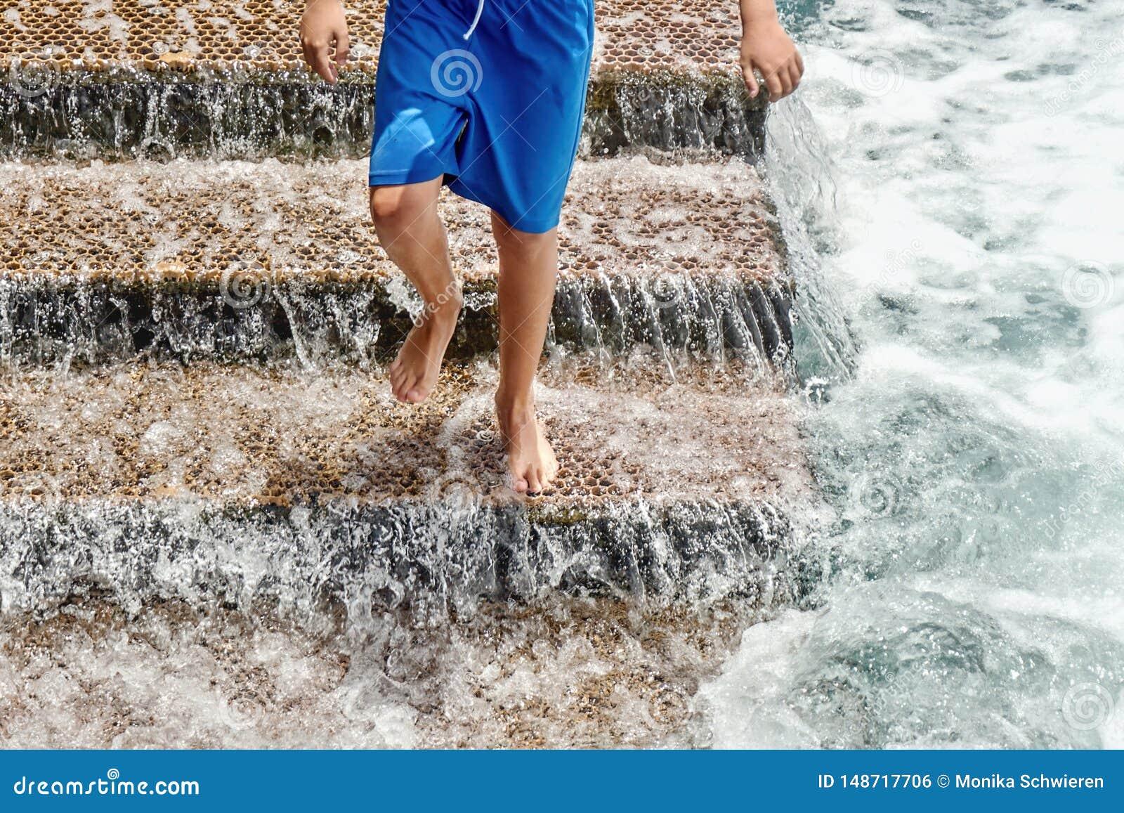 Ein Treppenhaus f?r Badeg?ste im Atlantik, ein junger Mann, der hinunter die Treppe springt