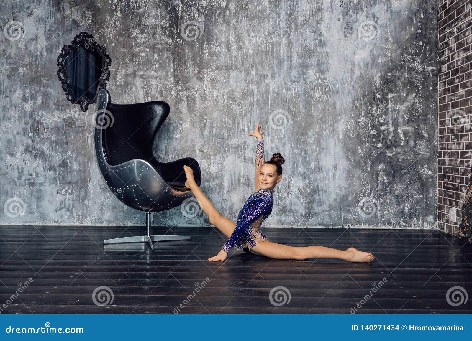 Ein Turner des jungen Mädchens in einer blauen Klage tut das Ausdehnen von Übung nahe dem Stuhl gegen die graue Wand und das Läch