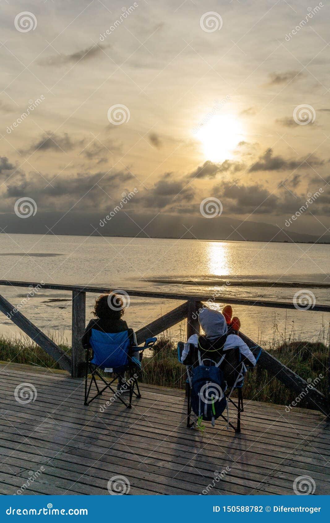 Ein unerkennbares Paar, das den Sonnenuntergang erwägend auf dem Meer sitzt