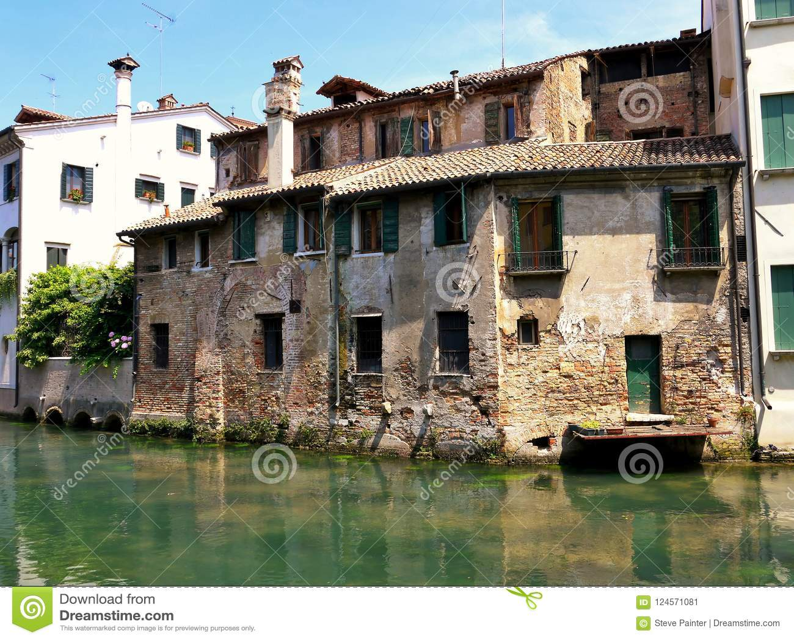 Ein verfallendes historisches Gebäude neben einem flowwing Fluss in Treviso