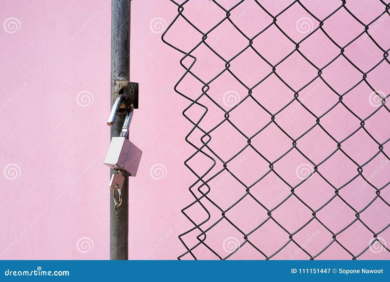 Ein Vorhängeschloß und ein Schlüssel am verdrahteten Tor