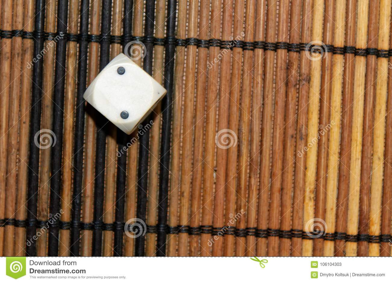 Ein weißer Plastikwürfel auf braunem Hintergrund des hölzernen Brettes Sechs Seitenwürfel mit schwarzen Flecken Nr. 2