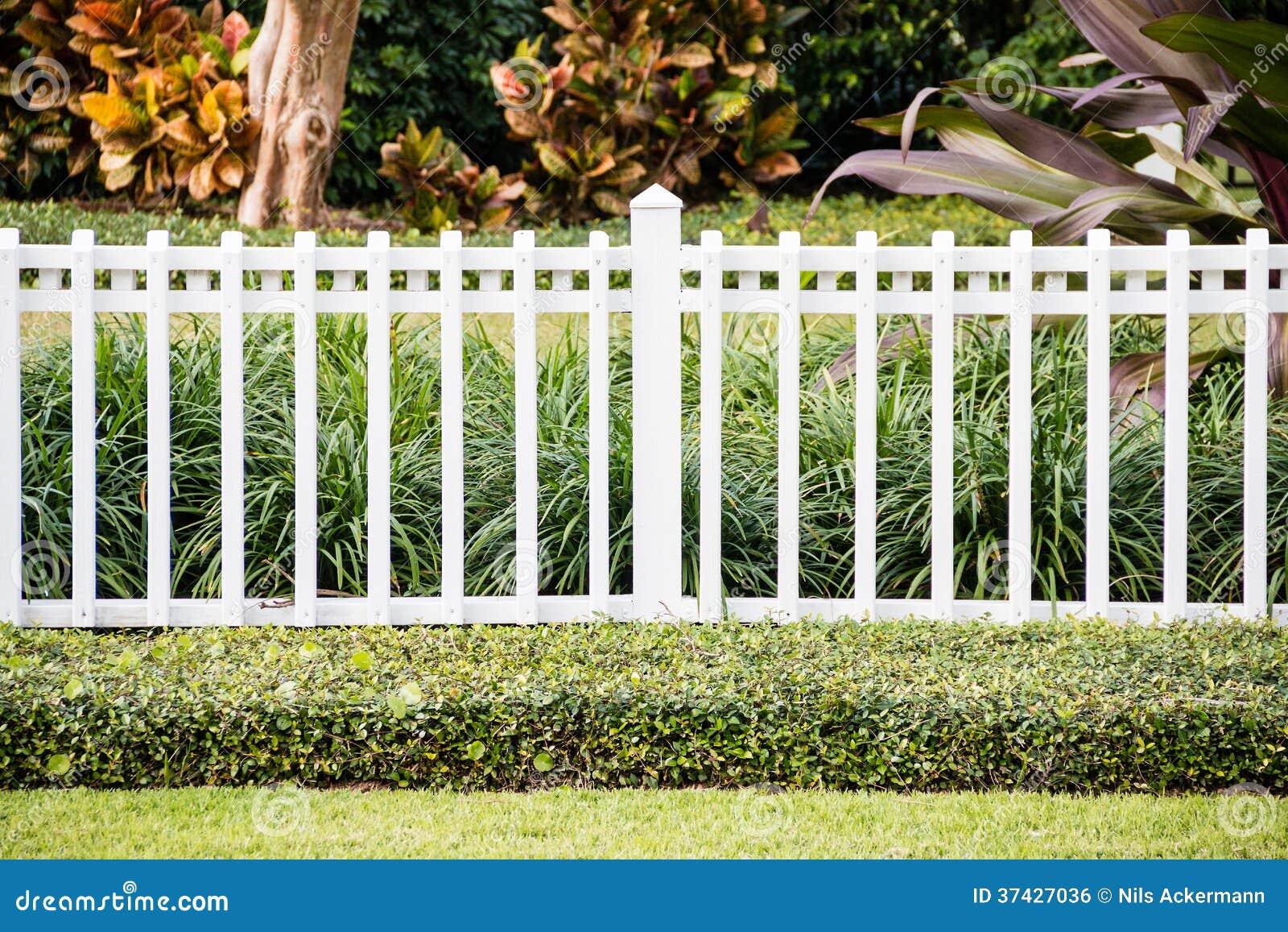 ein weißer zaun vor einem repräsentativhaus stockfoto - bild von