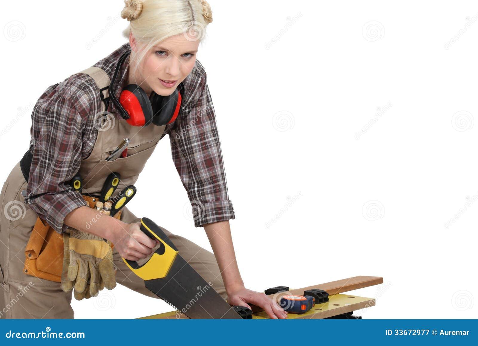 Ein weiblicher Tischler Sawing.