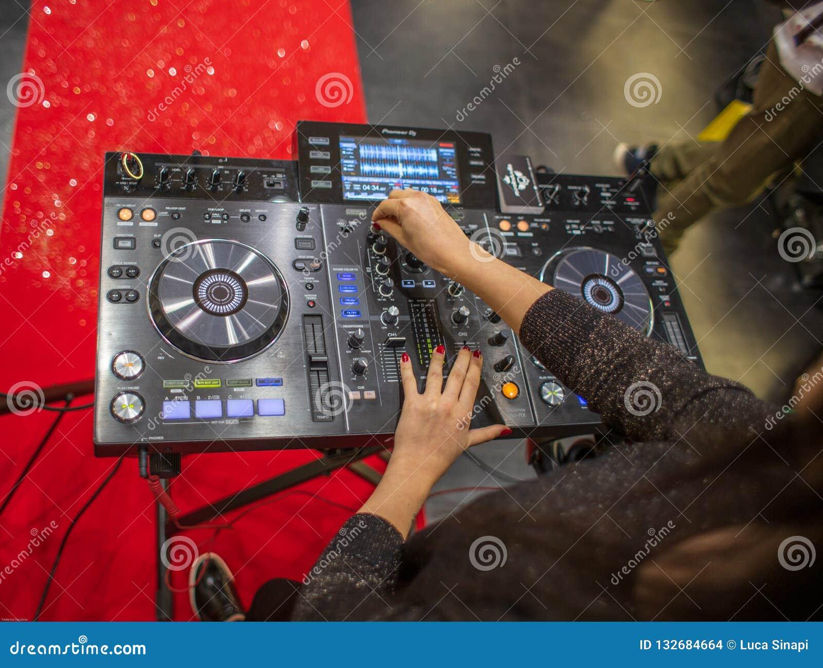 Ein weibliches DJ, das mit einer Pionierkonsole in Cagliari, Sardinien im November 2018 spielt
