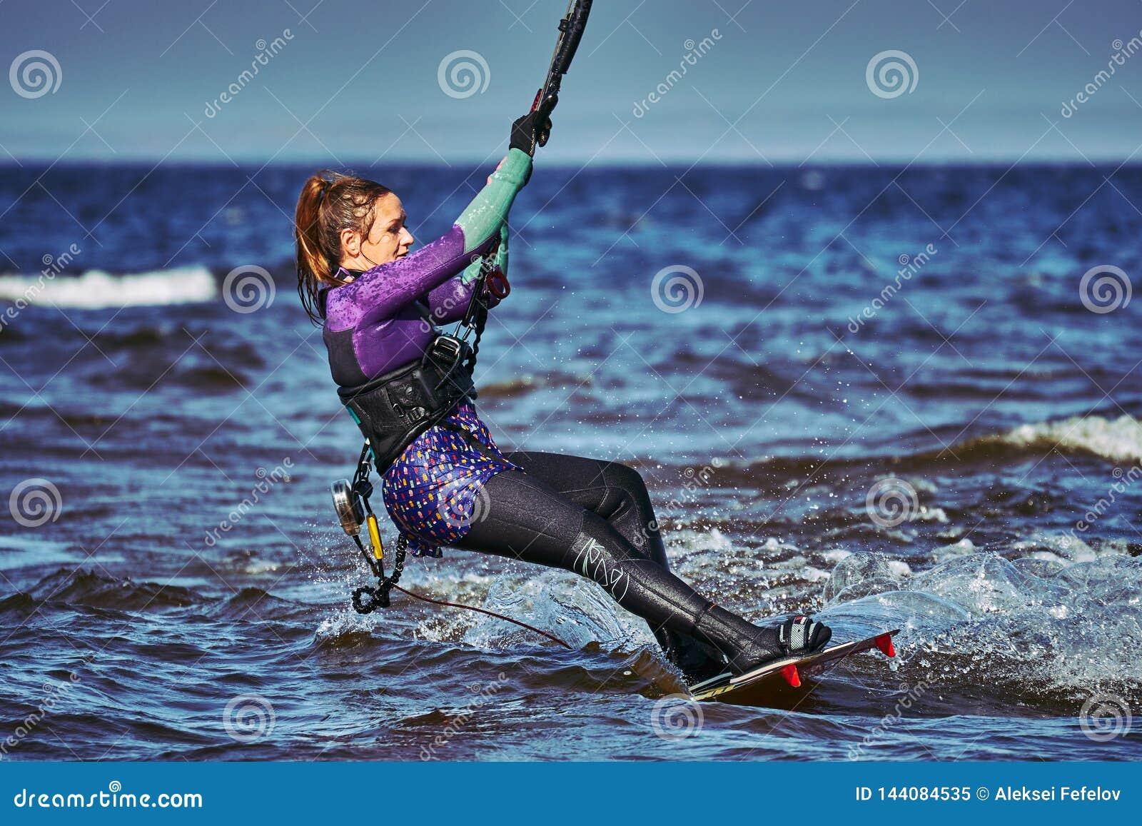 Ein weibliches kiter schiebt auf die Oberfl?che des Wassers Spritzt von der Wasserfliege auseinander