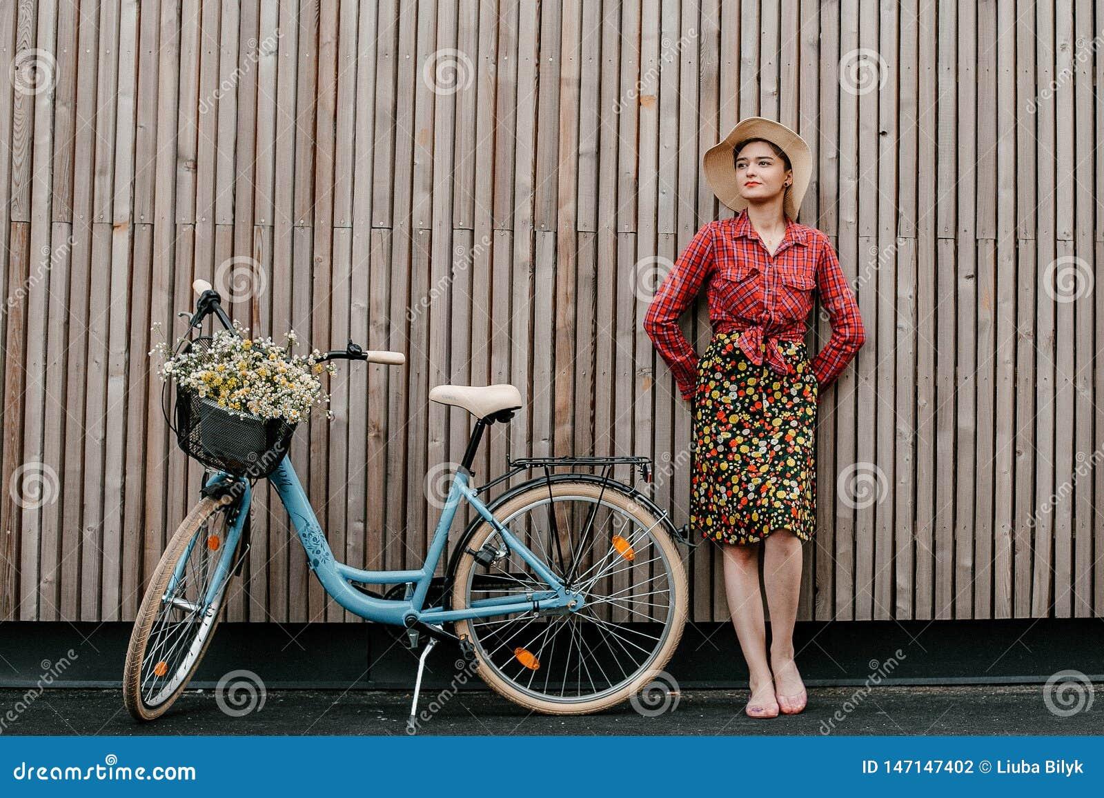 Ein wunderbares Mädchen reist mit dem Fahrrad Gehen in das Freien Schönheit mit einem Korb von Blumen Fahrradfahrt