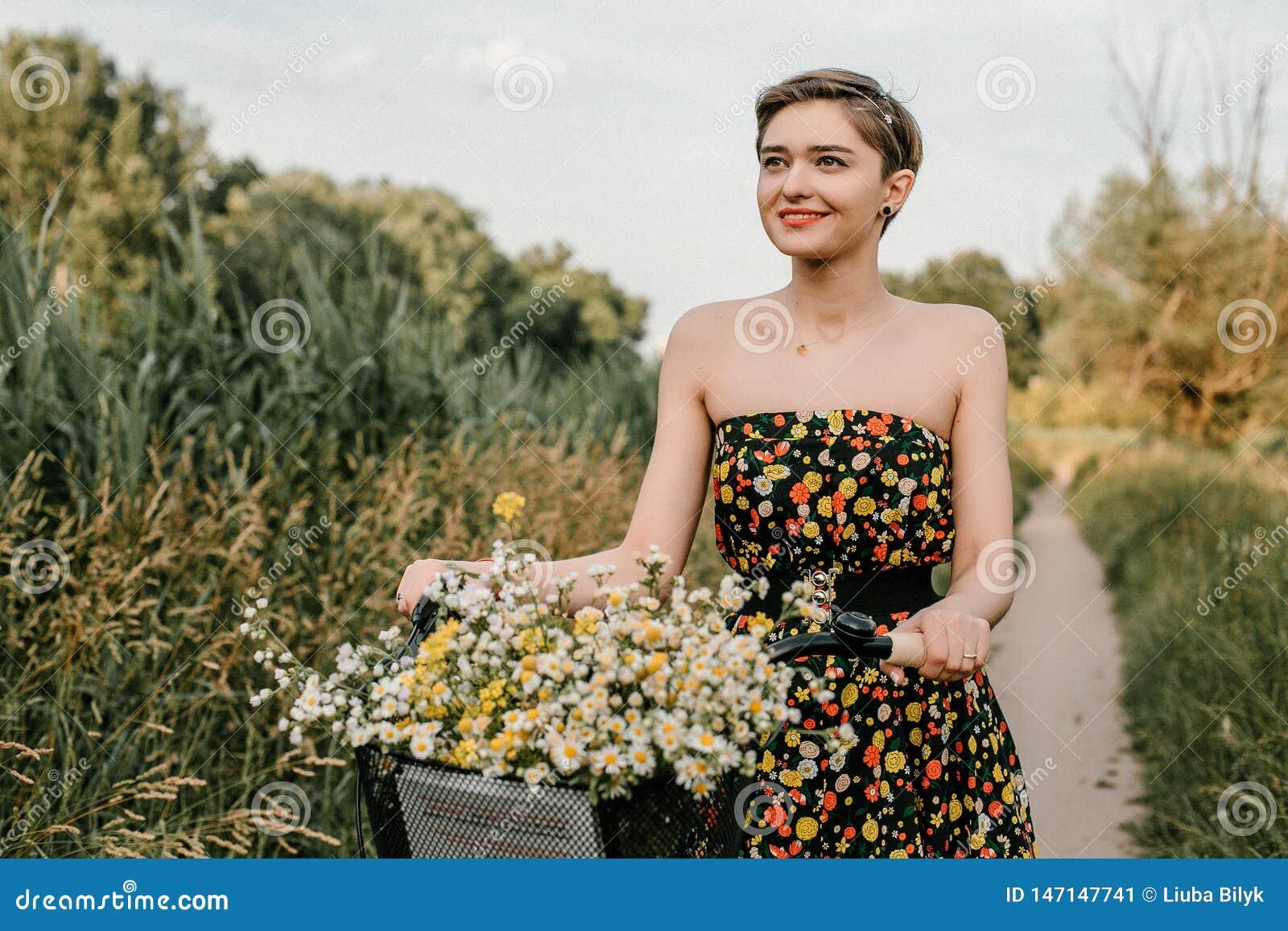 Ein wunderbares M?dchen reist mit dem Fahrrad Gehen in das Freien Sch?nheit mit einem Korb von Blumen Fahrradfahrt