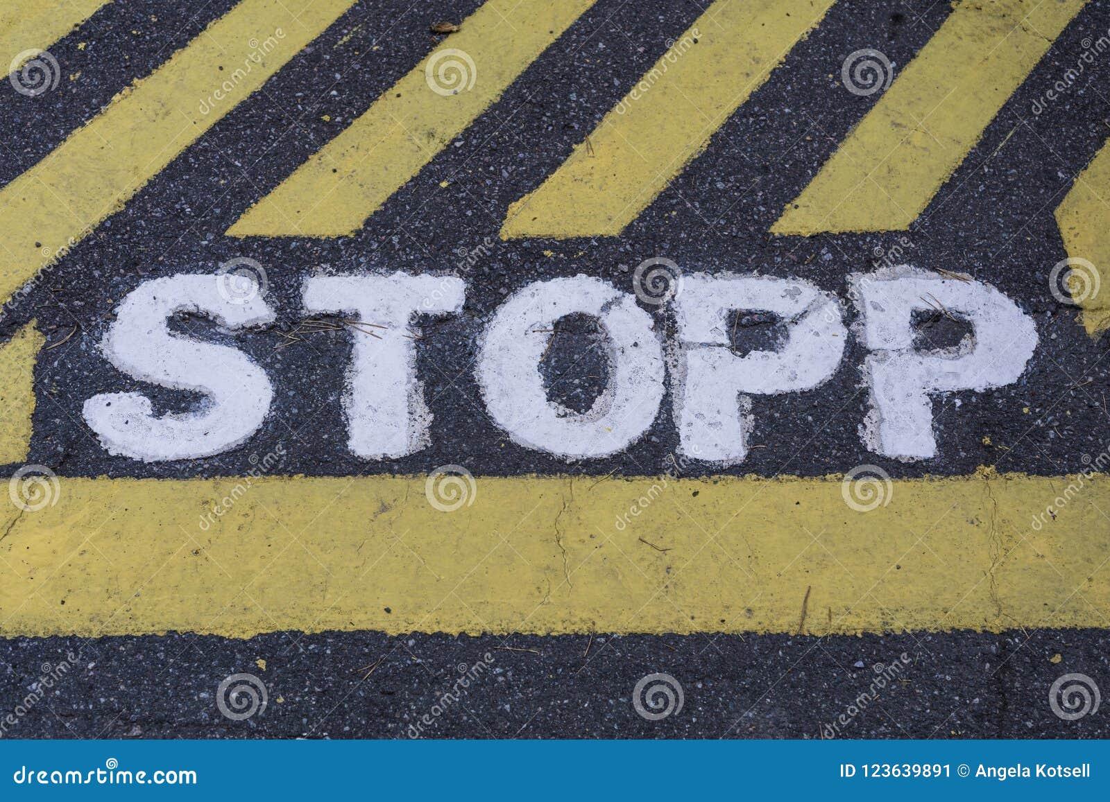 Eindeteken STOPP in Zweeds op asfalt wordt geschilderd dat