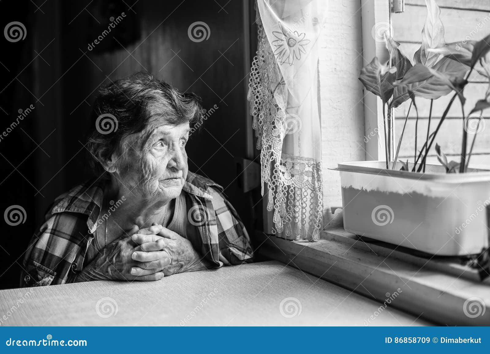 Eine ältere Dame sitzt traurig nahe dem Fenster seines alten Hauses