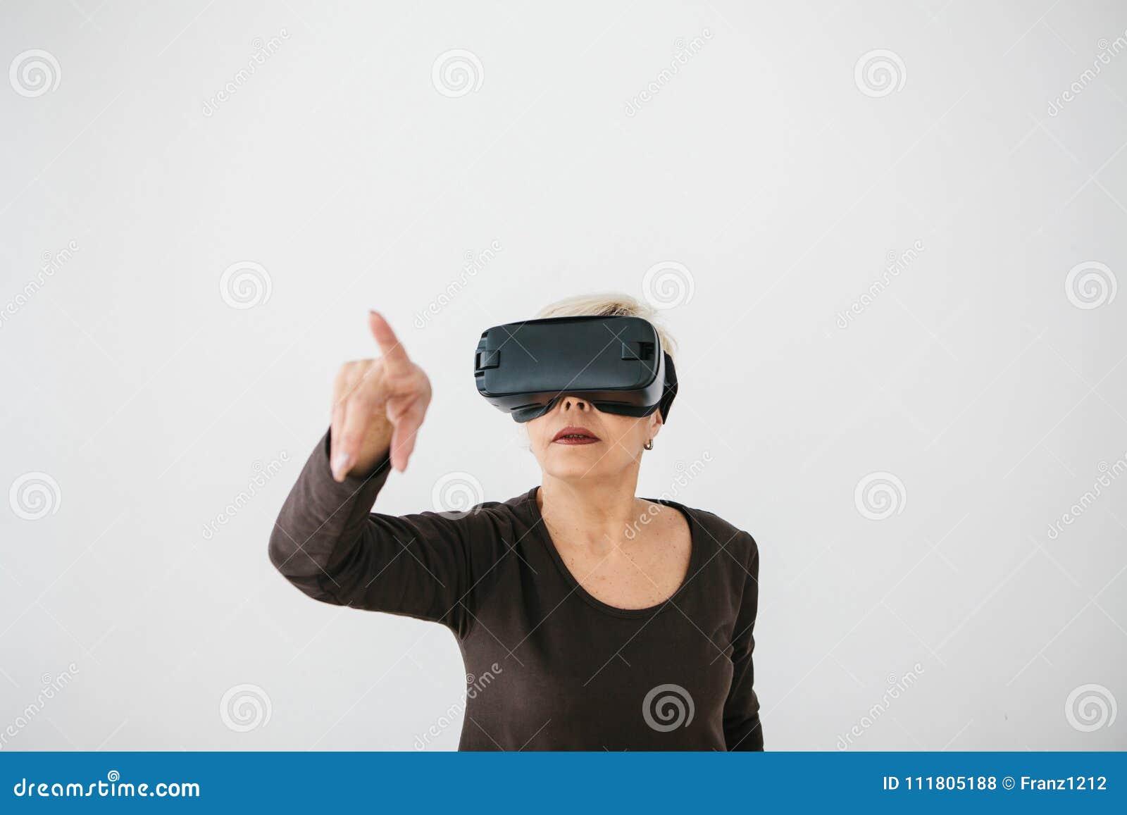 Eine ältere Frau in den Gläsern der virtuellen Realität Eine ältere Person, die moderne Technologie einsetzt