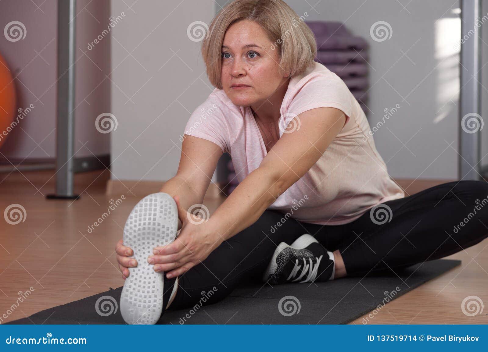 Eine ältere Frau nimmt an dem Ausdehnen an der Turnhalle teil