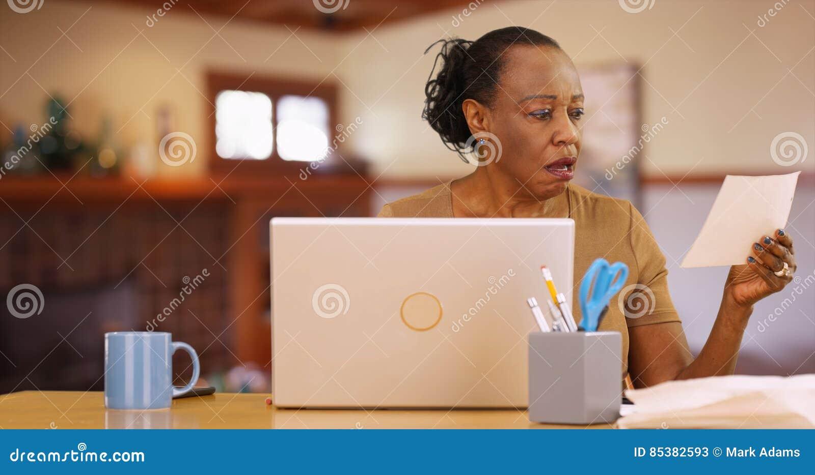 Eine ältere schwarze Frau, die vor dem Computer entsetzt durch Rechnungszahlungen sitzt