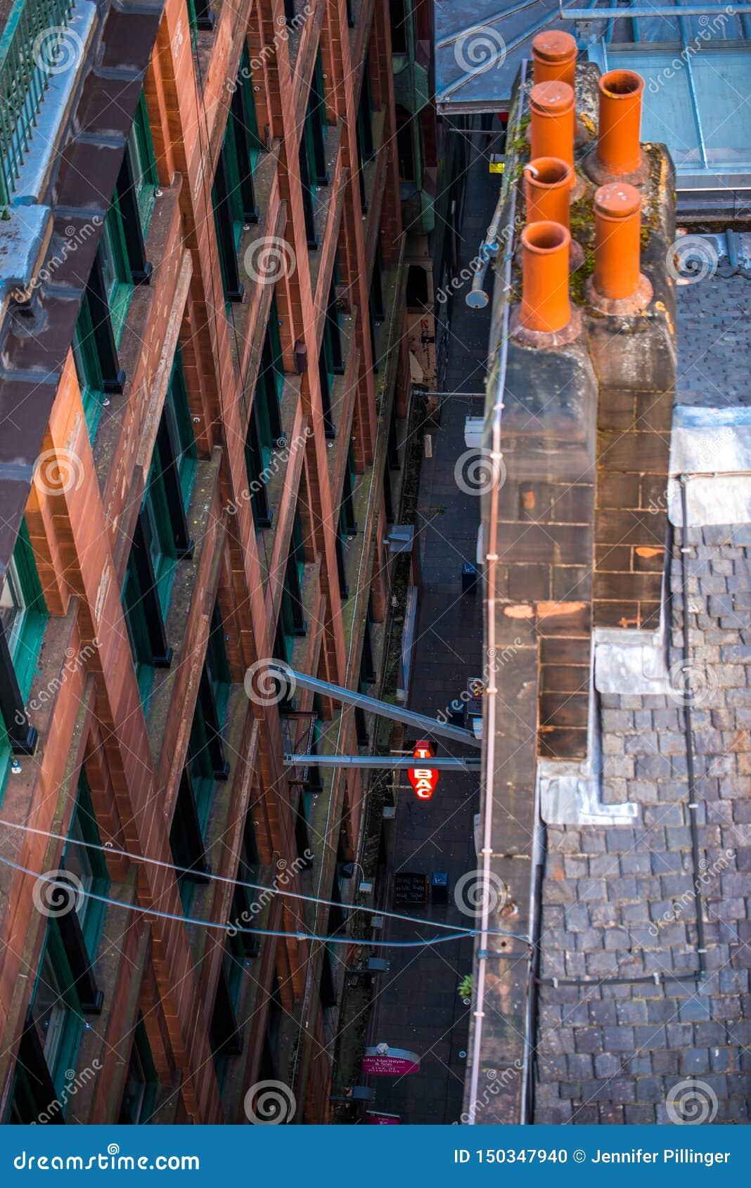 Eine abstrakte Ansicht, die unten auf einem schmalen Durchgang im Glasgow-Stadtzentrum, Schottland, Vereinigtes Königreich schaut