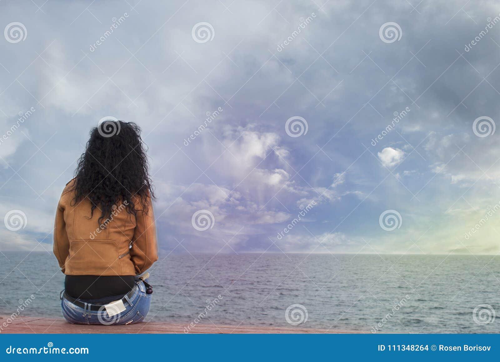 Eine allein stehende Frau auf dem Strand