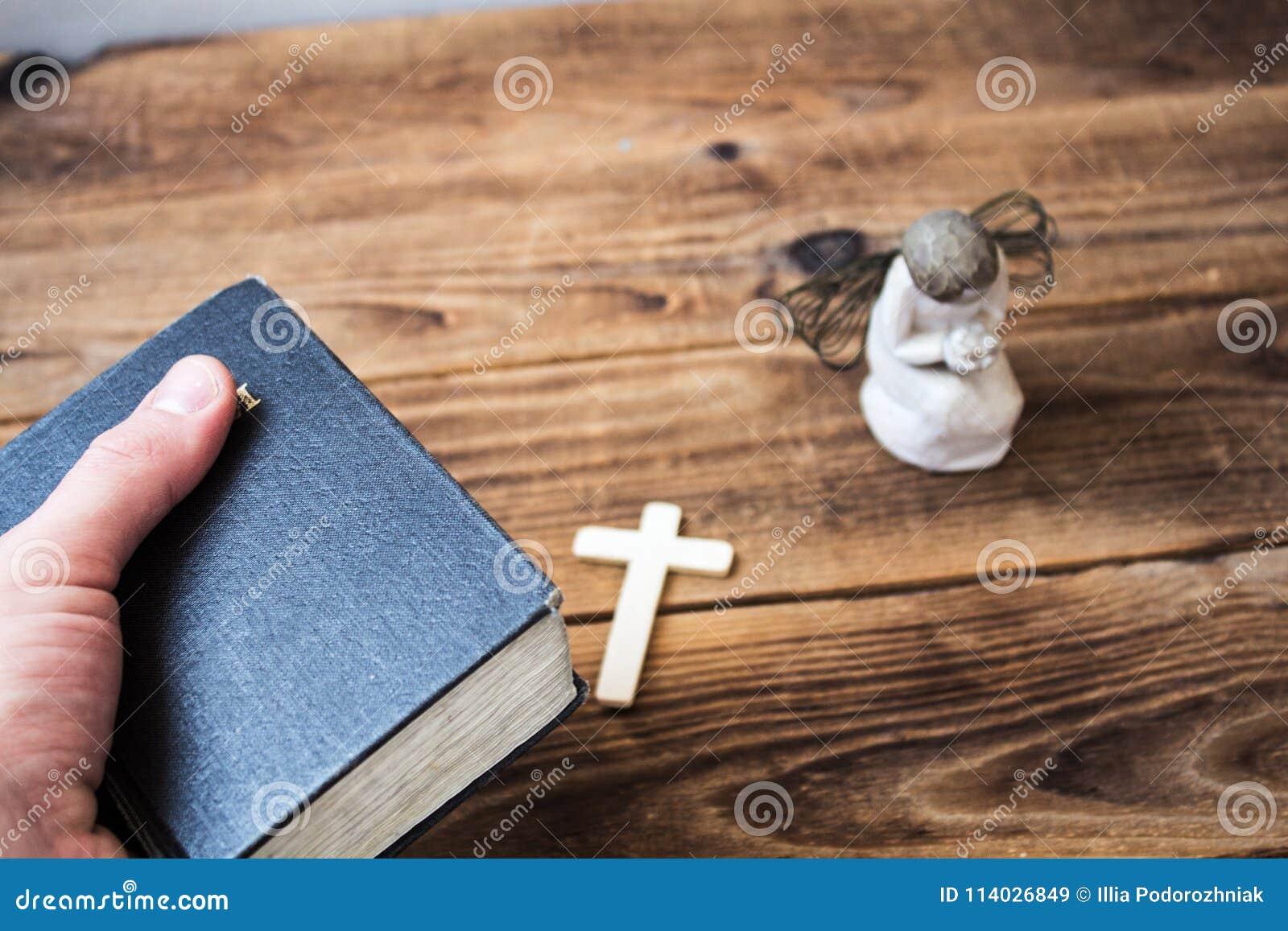 Eine alte Bibel des Engels in der Hand und Kreuz