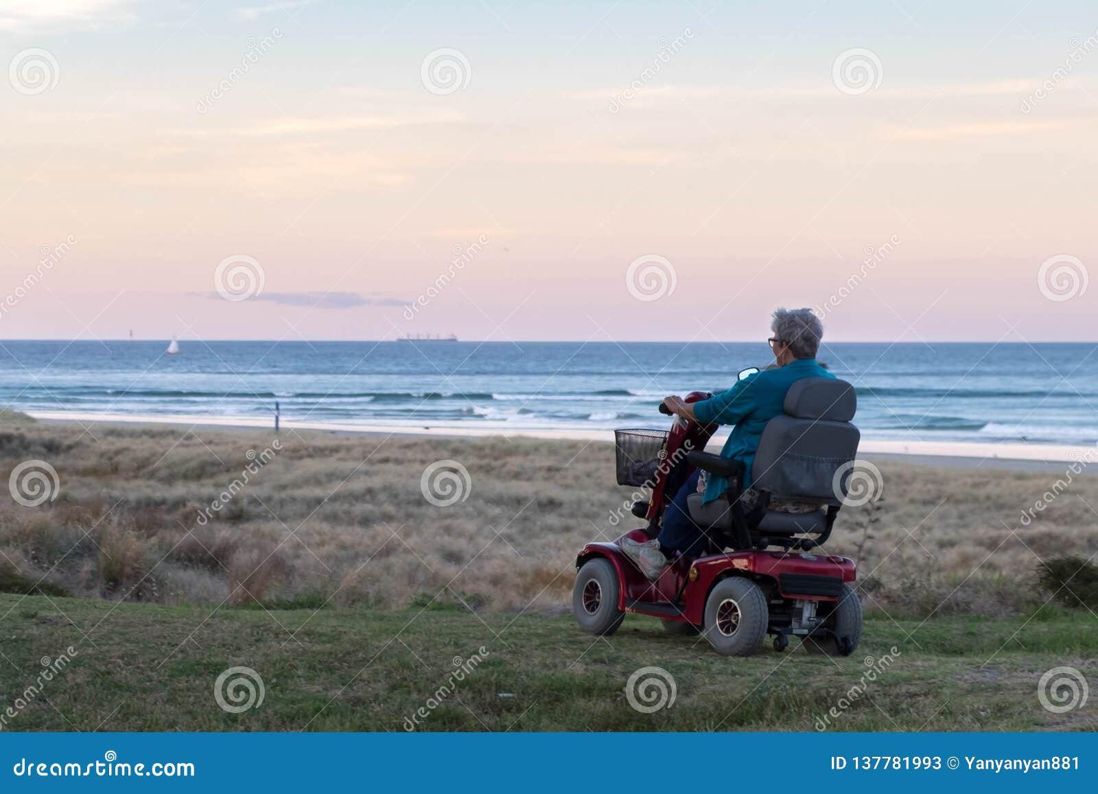 Eine alte Frau fährt auf einen elektrisch betriebenen Rollstuhl, der auf dem Strand zur Sonnenuntergangzeit, in einer einsamen At