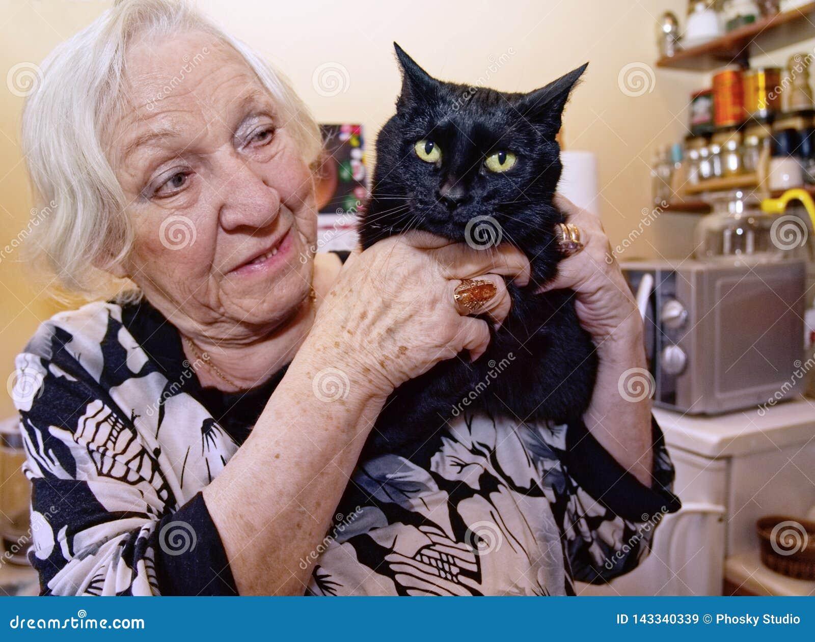 Eine alte Frau umarmt ihre Katze