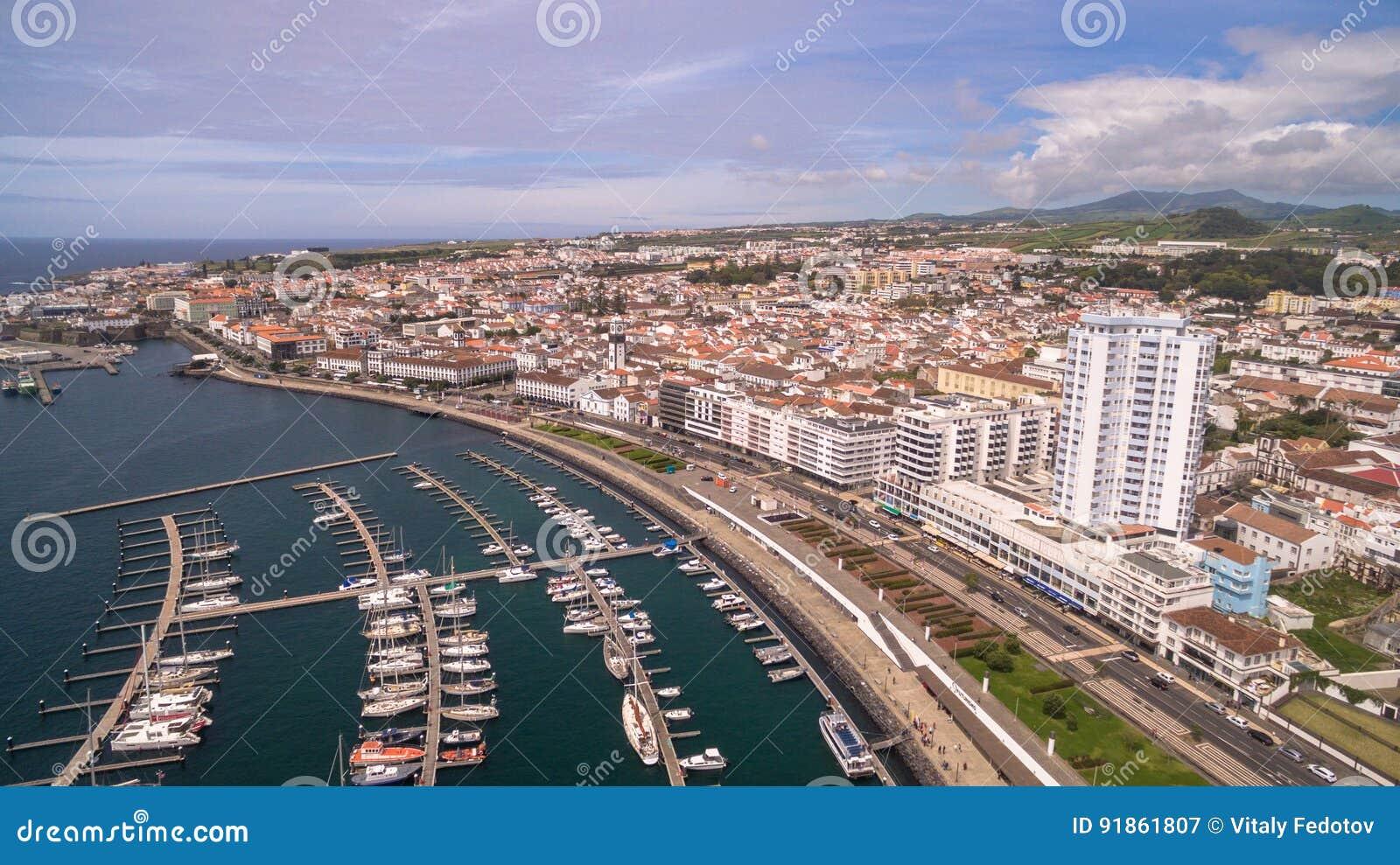 Eine Ansicht über Ponta Delgada vom Jachthafen, Sao Miguel, Azoren, Portugal Festgemachte Yachten und Boote entlang den Hafenpier