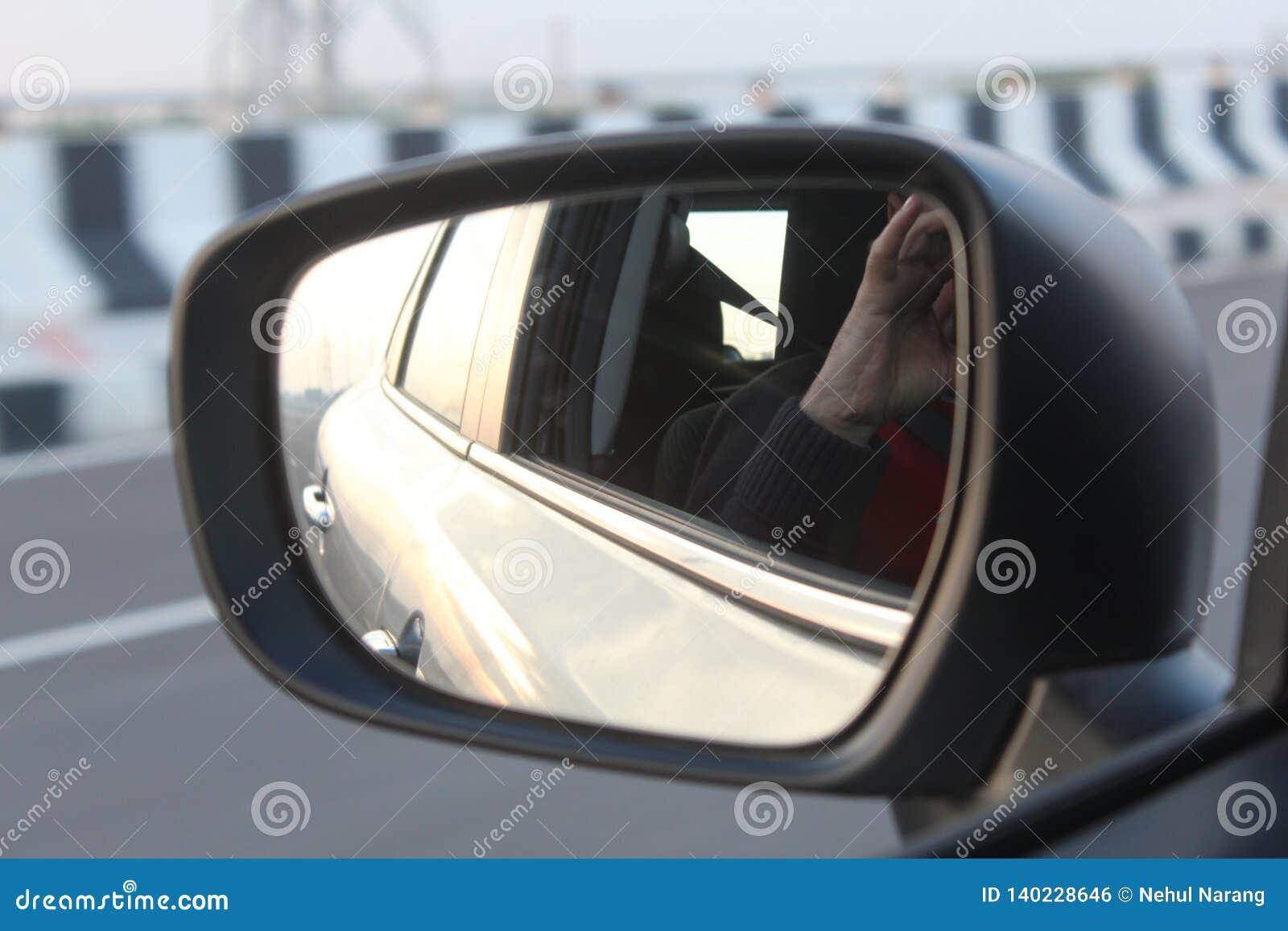 Eine Ansicht des Seitenansichtspiegels des Autos auf einer Landstraße