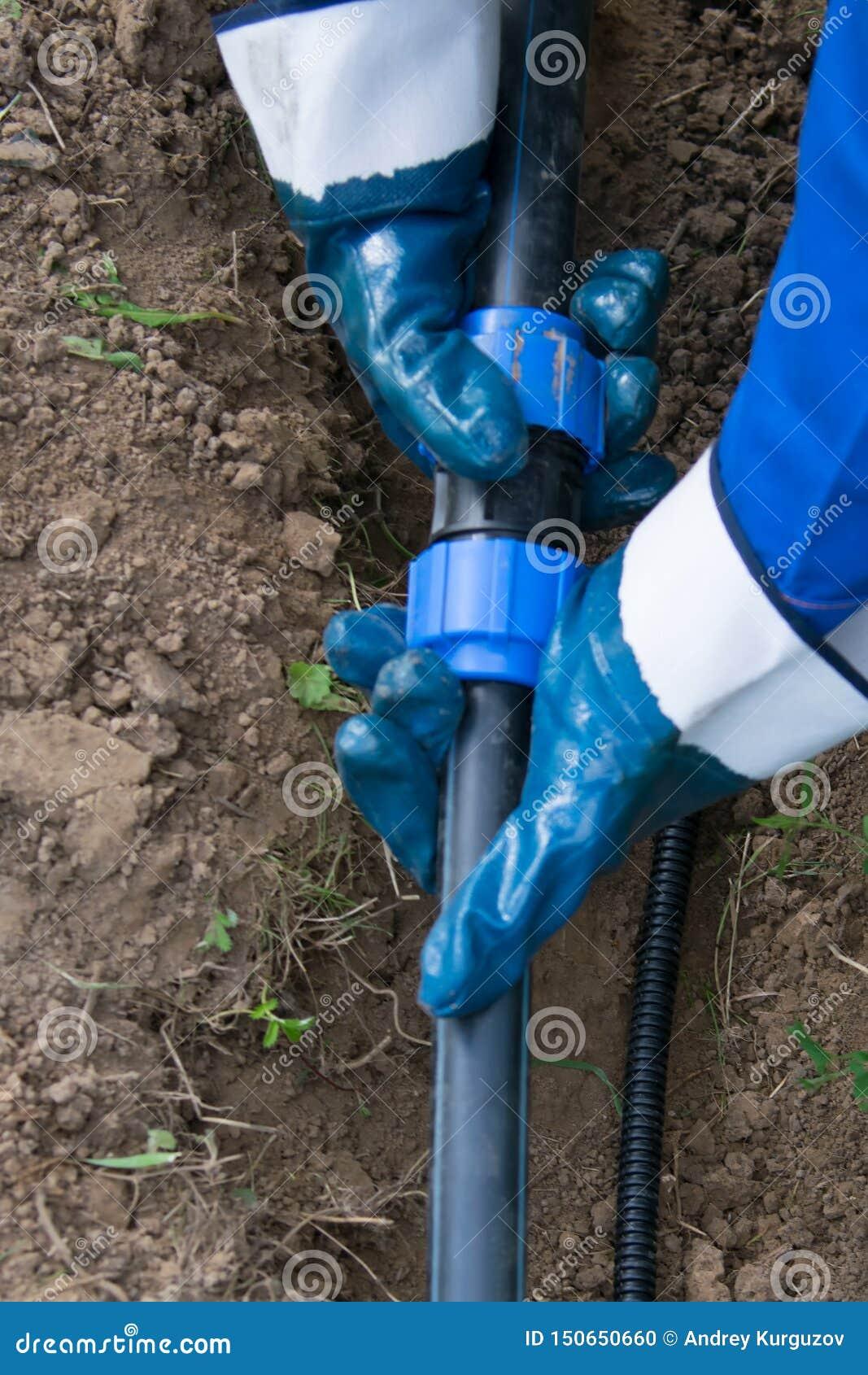 Eine Arbeitskraft legt in einen gegrabenen Graben, ein Abflussrohr