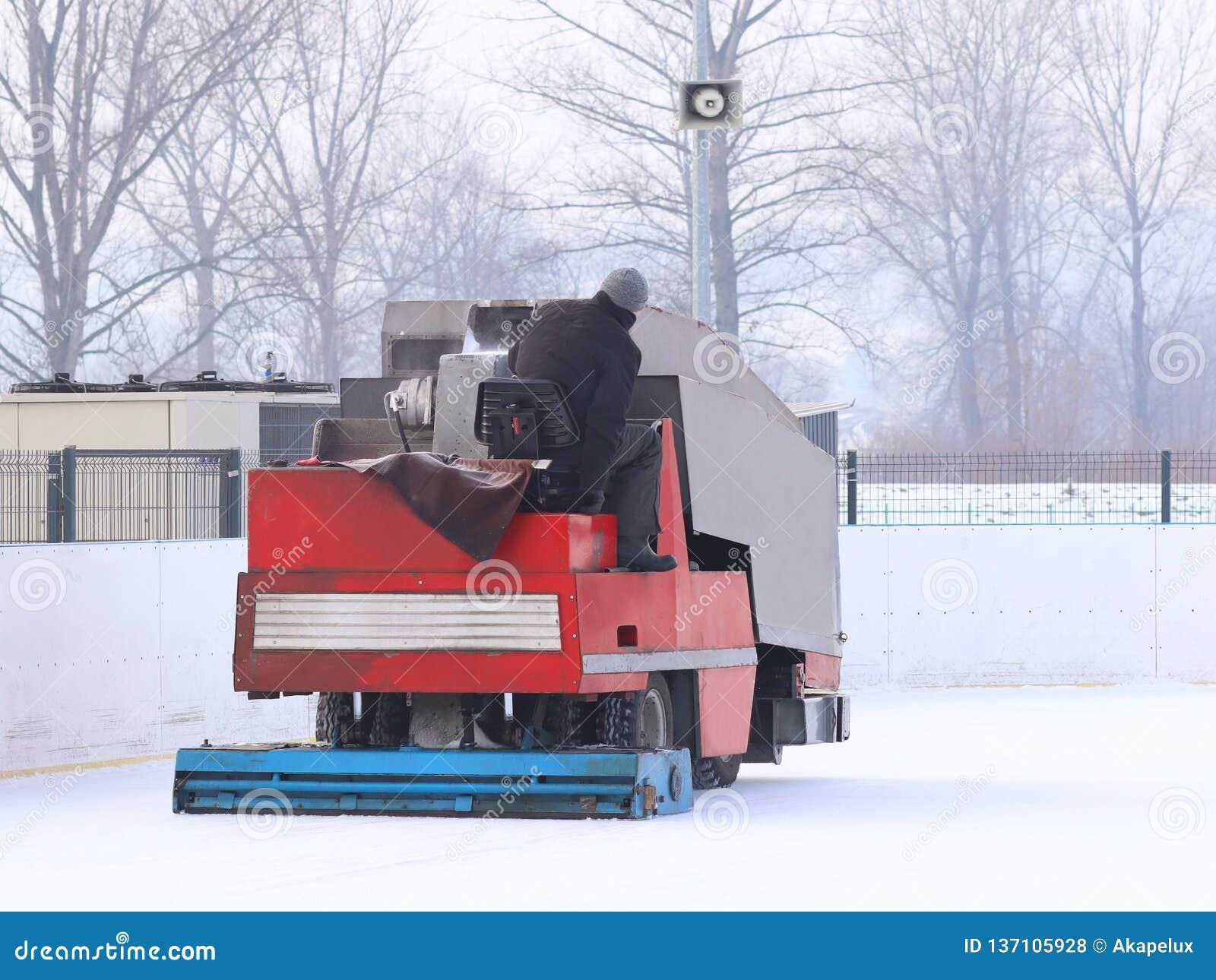 Eine Arbeitskraft schießt eine maintenant Maschine des speziellen Eises auf eine Sporteisbahn Kochen des Platzes für den Eislauf