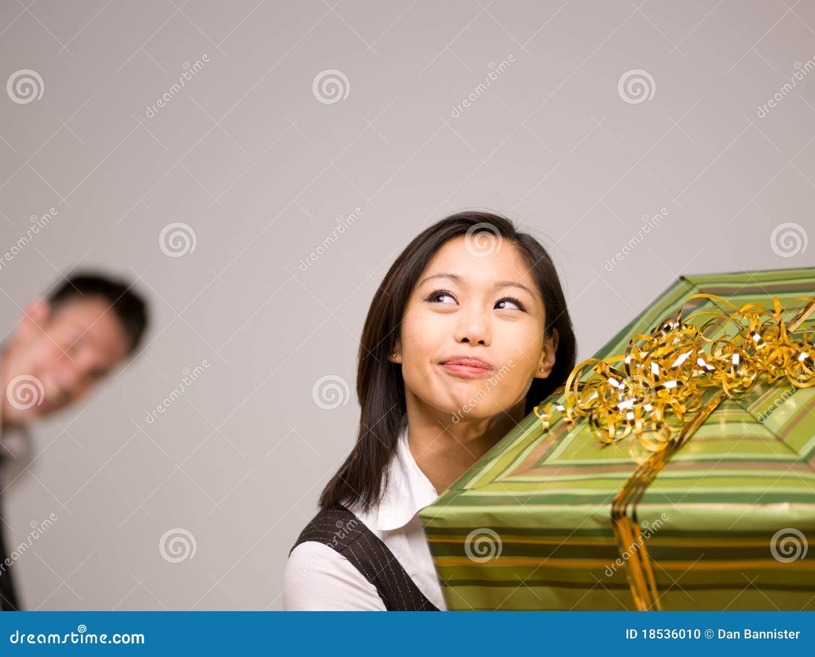 eine asiatische frau und ein geschenk stockfoto bild von erregen freude 18536010. Black Bedroom Furniture Sets. Home Design Ideas