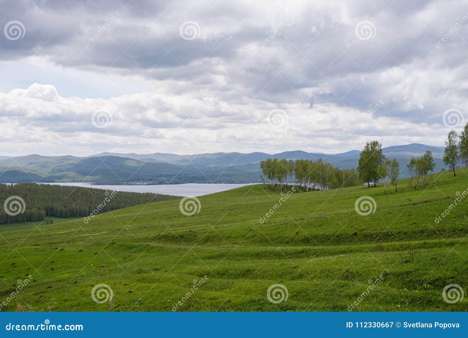 Eine bewölkte Frühlingslandschaft mit einem blühenden Hügel und einem See im Abstand