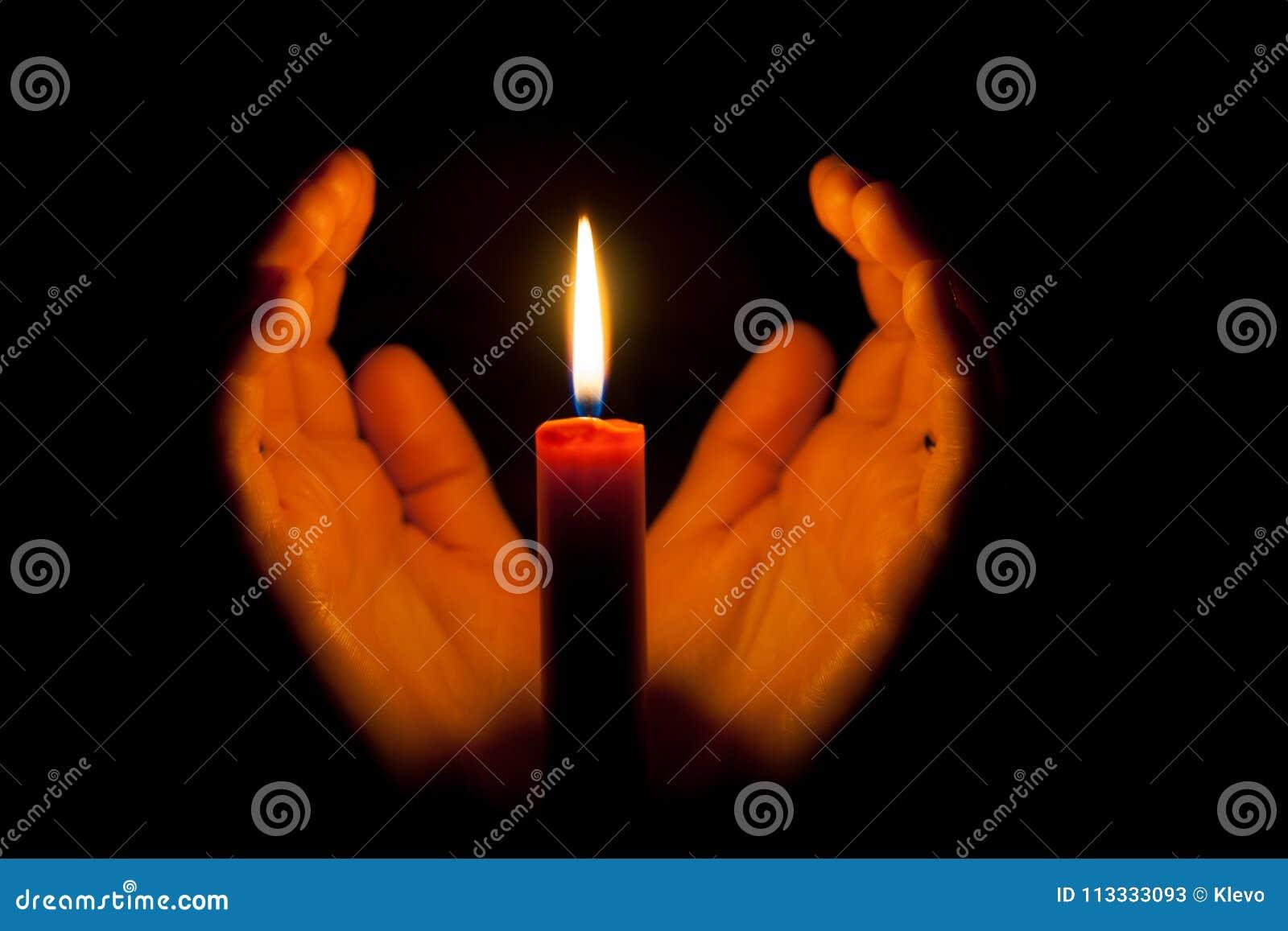 Eine brennende Kerze nachts, umgeben durch die Hände einer Frau Symbol des Lebens, der Liebe und des Lichtes, des Schutzes und de
