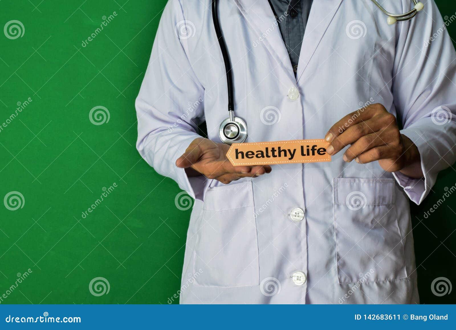 Eine Doktorstellung, halten den gesunden Lebenpapiertext auf grünem Hintergrund Medizinisches und Gesundheitswesenkonzept