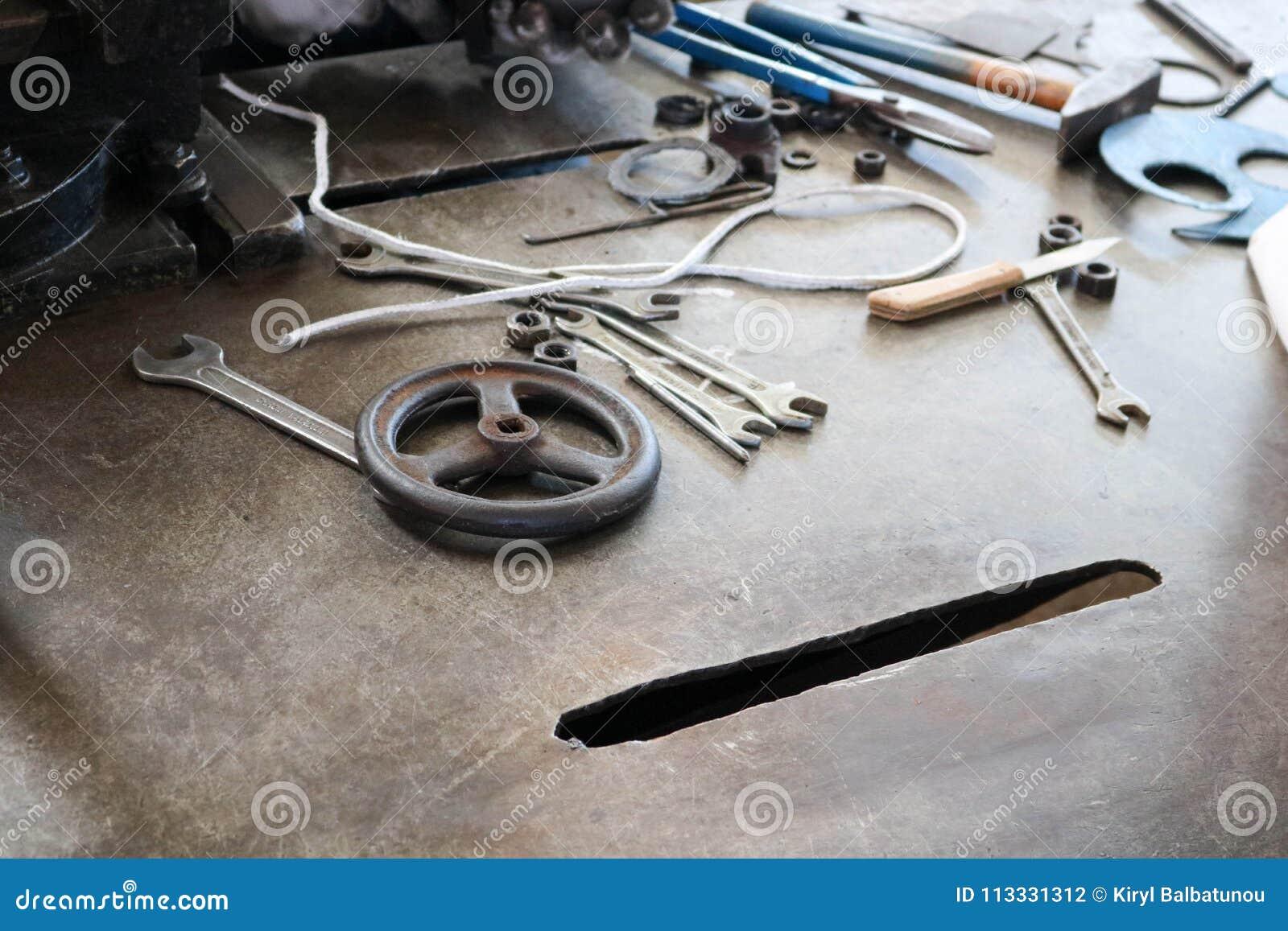 Eine Eisentabelle mit einem Metallverarbeitungswerkzeug, Schlüssel, Hämmer, Schraubenzieher, Quetschwalzen, Messer, Ventile in de