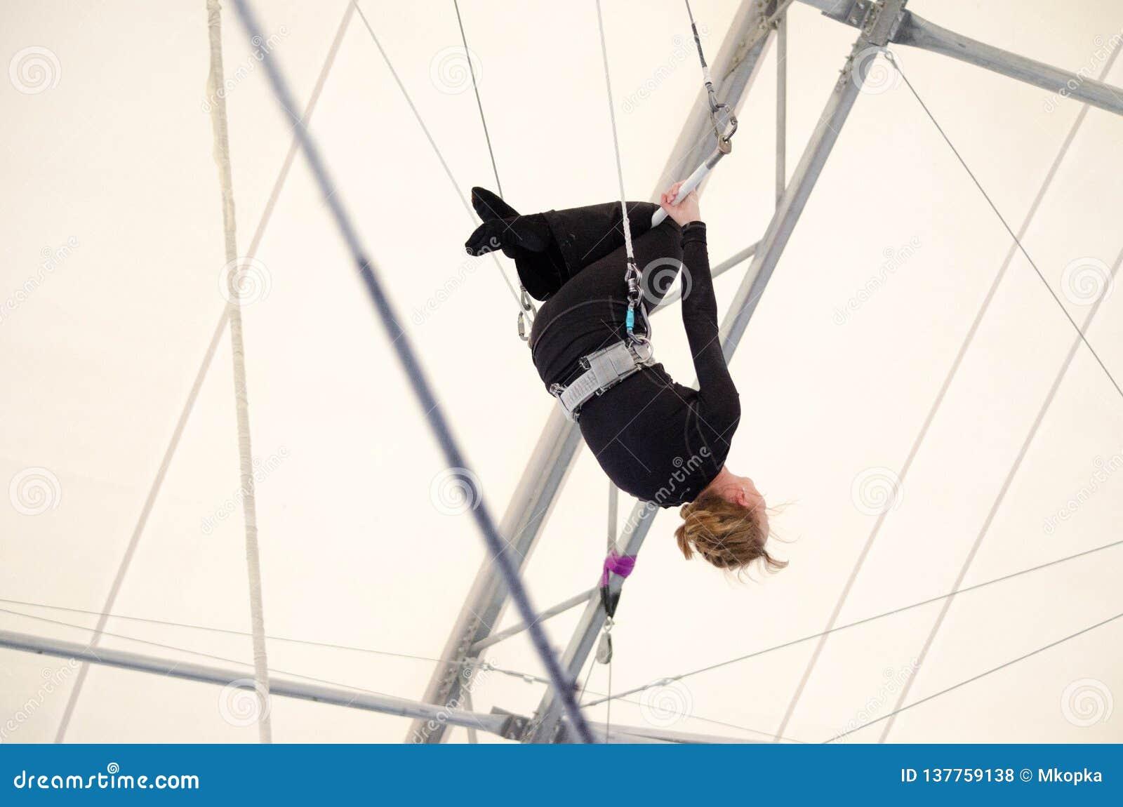 Eine erwachsene Frau hängt an einem fliegenden Trapez an einer Innenturnhalle Die Frau ist ein Amateurtrapezkünstler