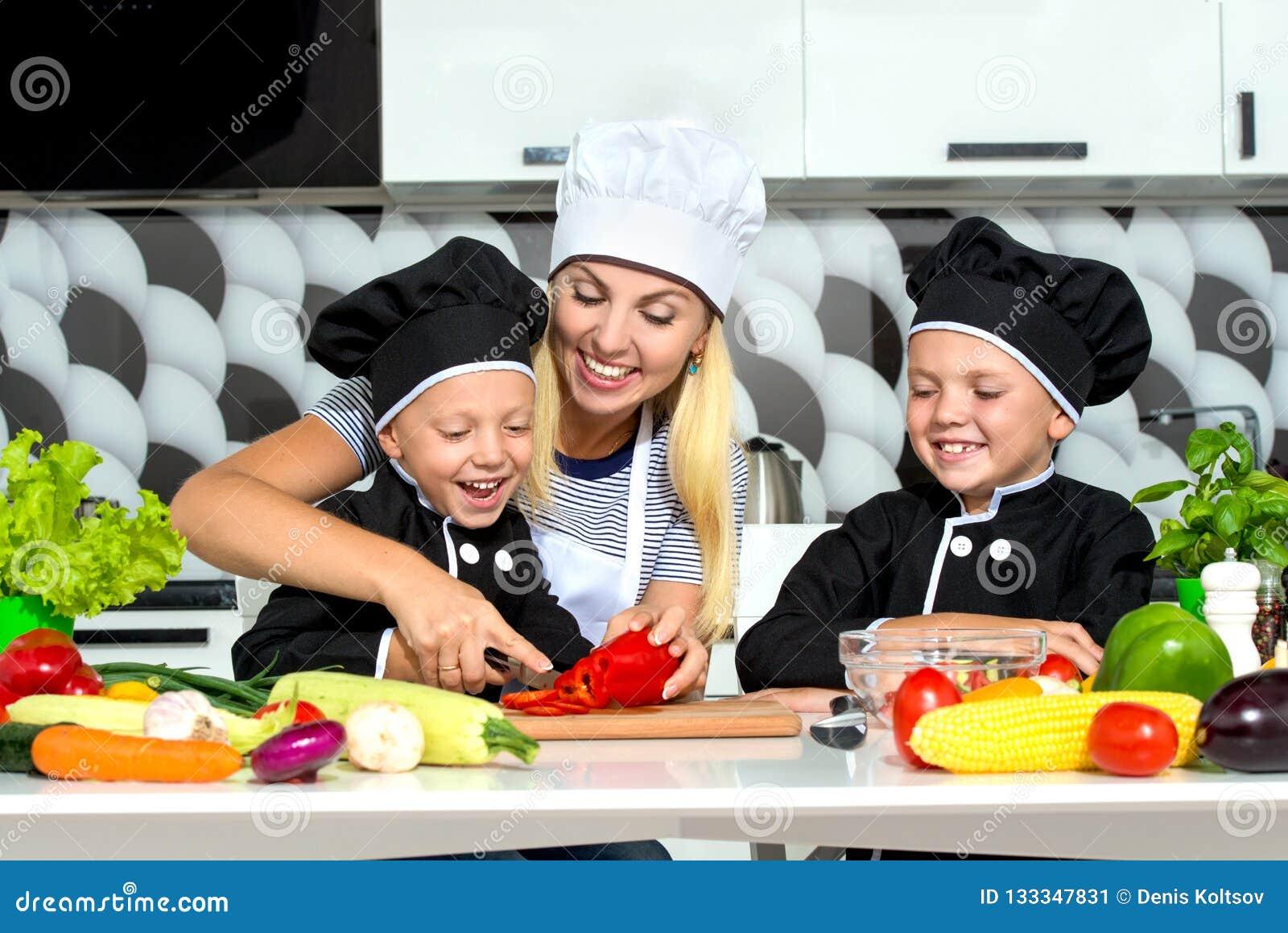 Eine Familie von Köchen Gesundes Essen Mutter und Kinder bereitet Gemüsesalat in der Küche zu