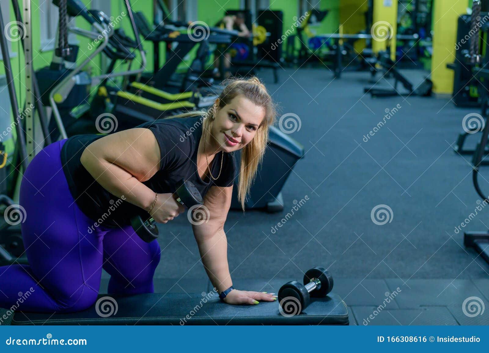 Eine Fettleibige Frau Trainiert Mit Den Mulden Auf Einer Bank Im Fitnessraum Die Fette Blondine