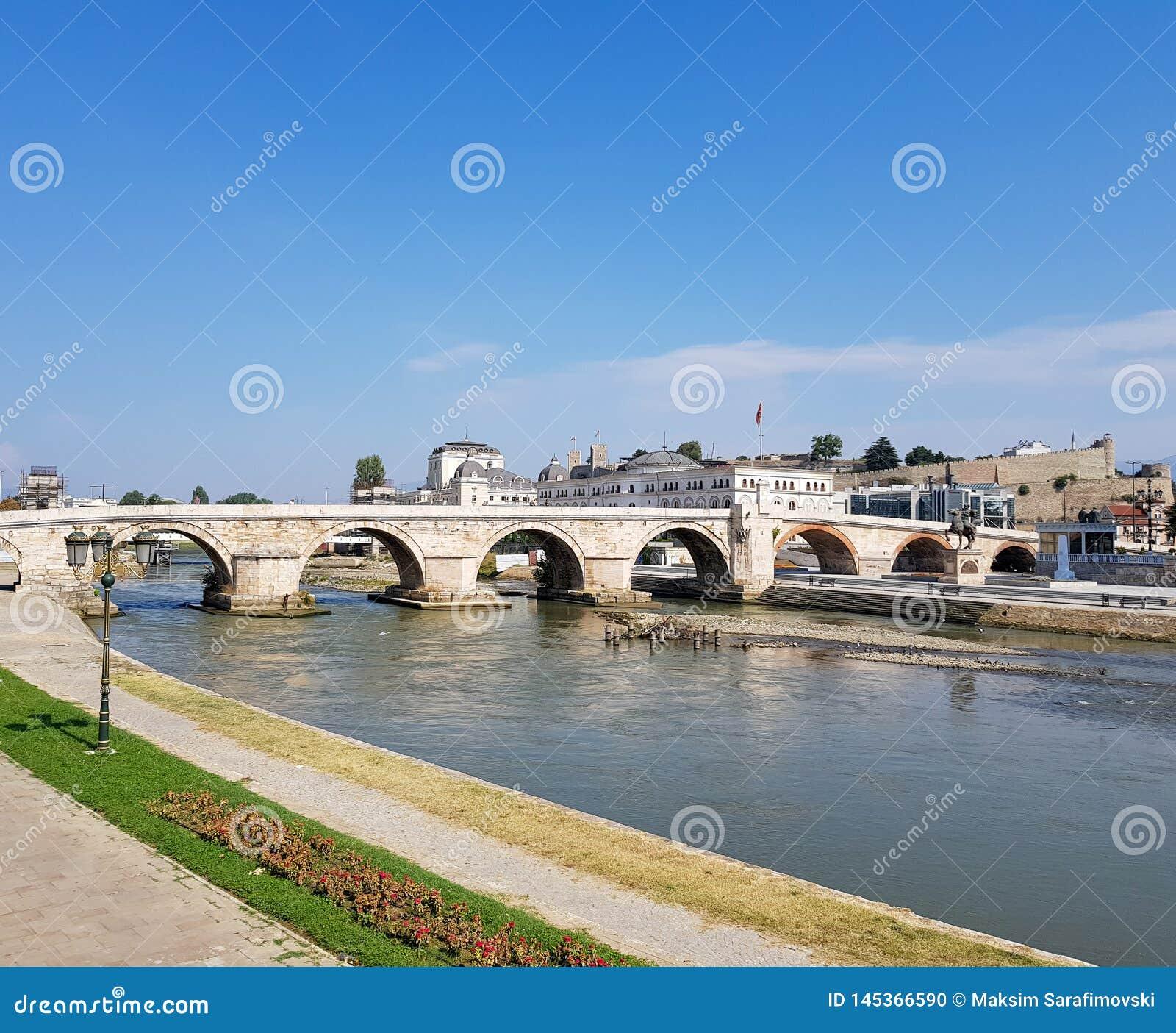 Eine Fotografie von Fluss überschreiten unter Steinbrücke