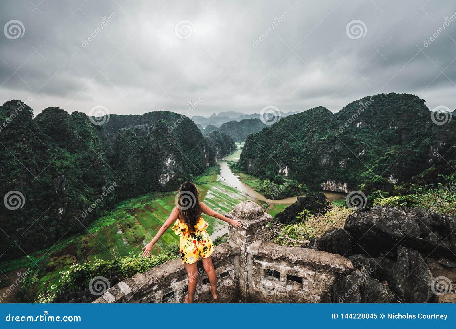 Eine Frau übersieht die Berge von Nord-Vietnam von Hang Mua, ein populärer wandernder Bestimmungsort